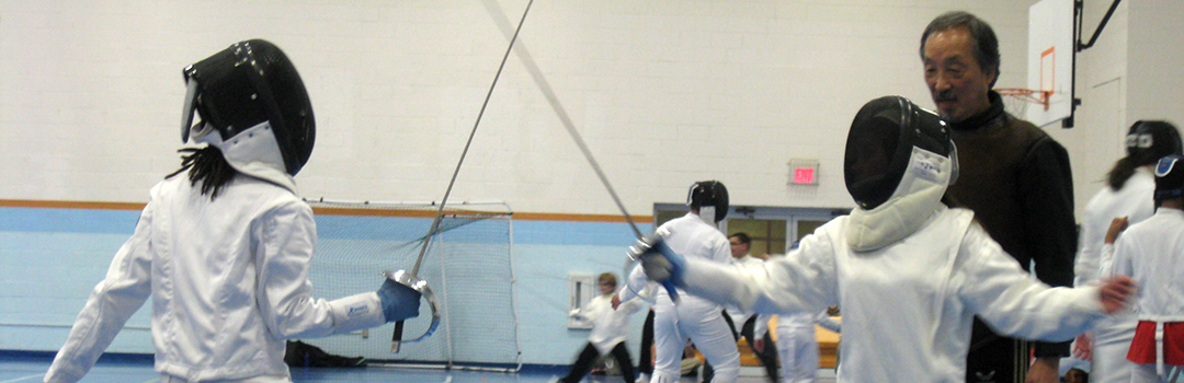 Two sabre fencers participating in group lessons.